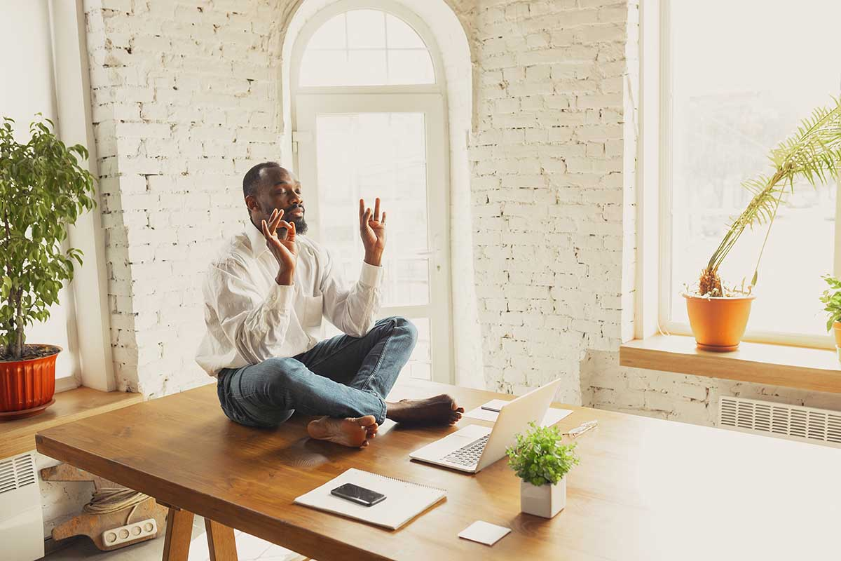 Young african-american man doing yoga at home while being quarantine and freelance working